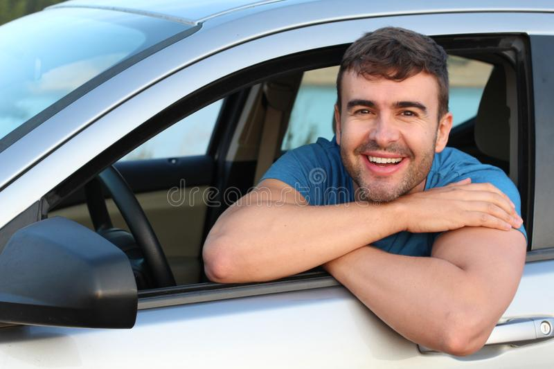 Handsome man satisfied with his automobile.  stock image