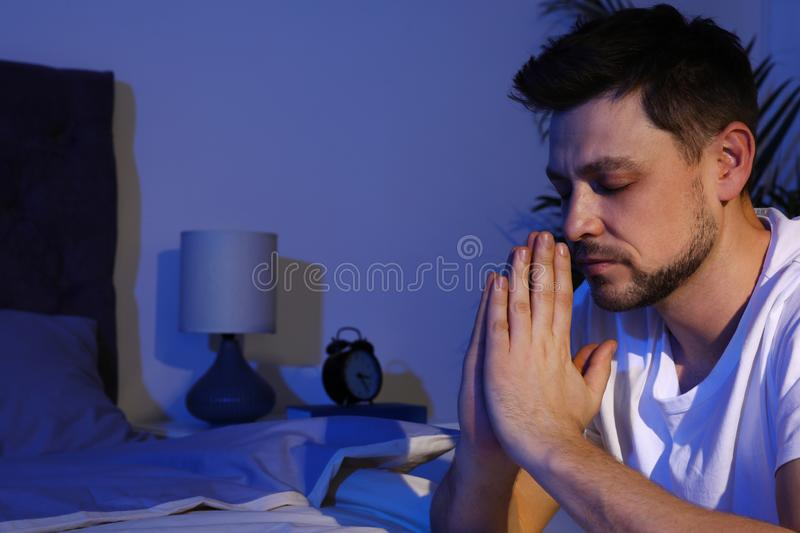 Handsome man saying bedtime prayer in dark room at night. Space for text stock image