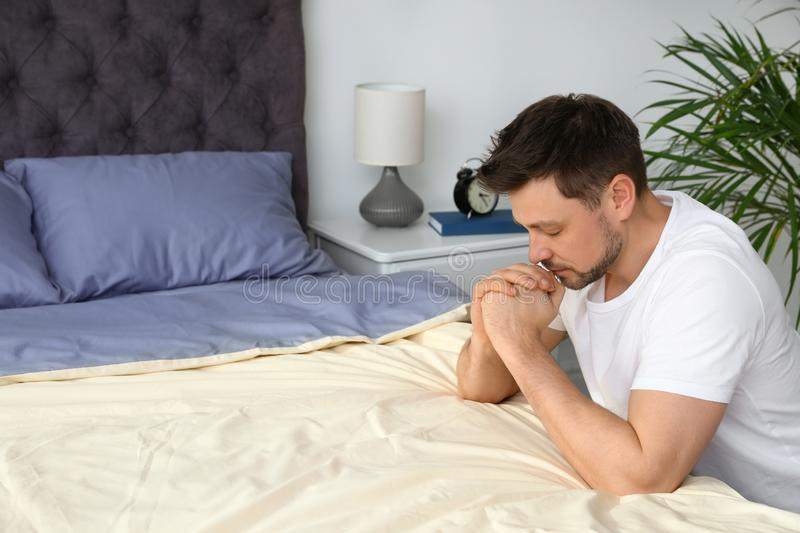 Handsome man saying bedtime prayer at home. Space for text royalty free stock images