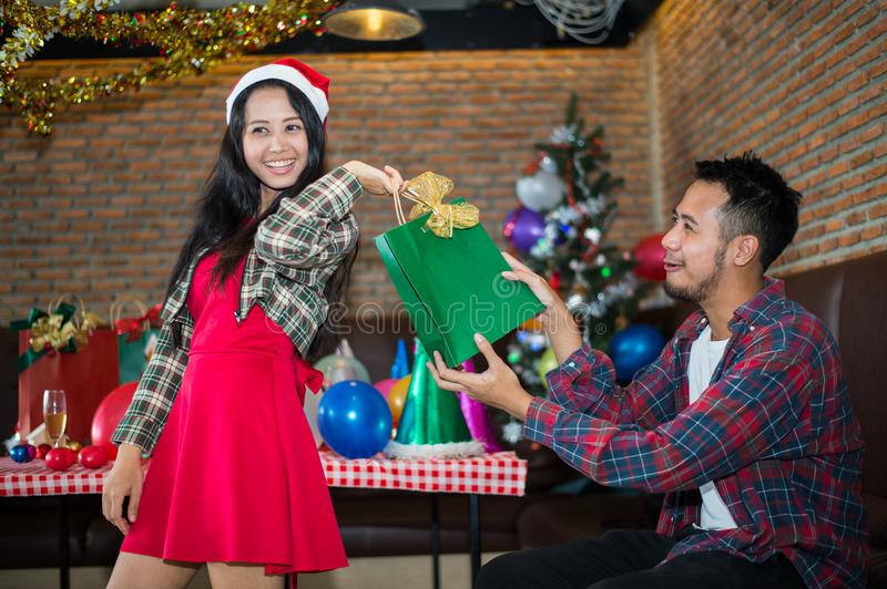 Handsome man sent green gift bag to beautiful woman, who wear red dress and santa claus hat at the party. Handsome men sent green gift bag to beautiful woman stock photo