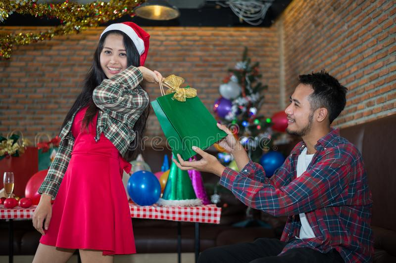 Handsome man sent green gift bag to beautiful woman, who wear red dress and santa claus hat at the party. Handsome men sent green gift bag to beautiful woman royalty free stock photos