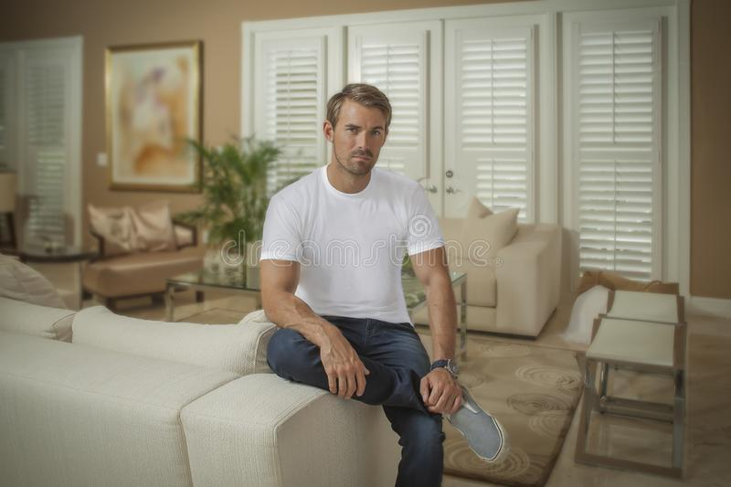 A handsome man sets on the arm of the couch crossed leg looks at the camera royalty free stock photography