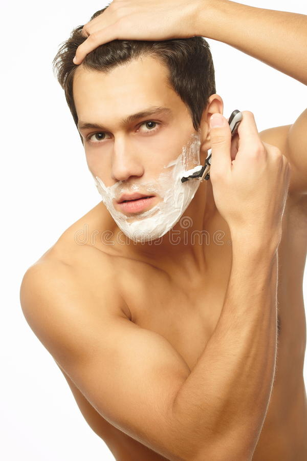 Handsome man shaving as part of morning routine. Portrait of a young handsome man shaving as part of his morning routine. isolated on white royalty free stock photos