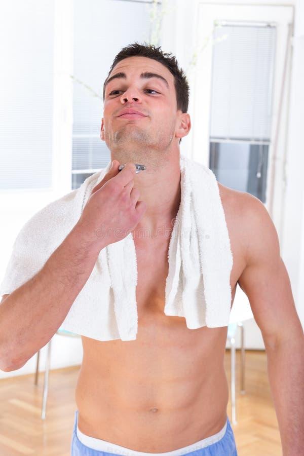 Handsome man shaving beard with razor in hand stock image