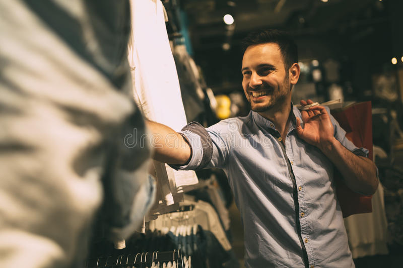 Download Handsome Man Shopping For Clothes Stock Photo - Image of choice, consumer: 74946506