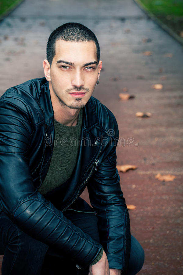 Handsome man short hair style outdoors. Handsome young model outdoors. Intense look, leather jacket. Light eyes. Road with autumn scene behind him. Some leaves royalty free stock images