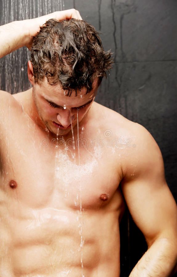 Handsome man at the shower. Handsome muscular man at the shower stock photo