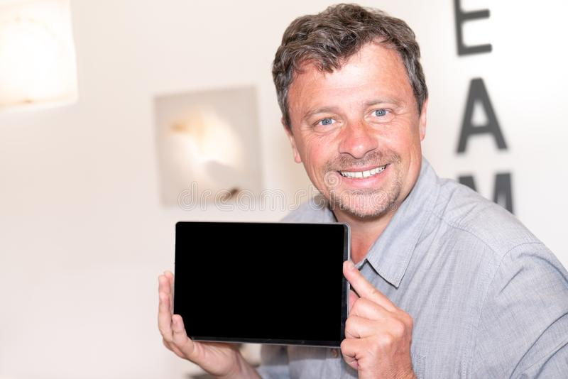 Handsome Man Showing Tablet Screen at home in studio Shot royalty free stock photos