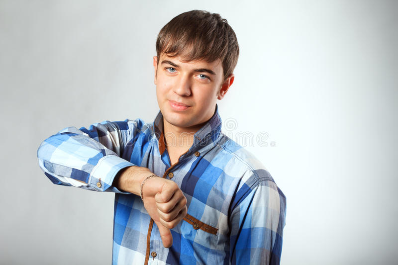 Handsome man showing thumb down stock photo