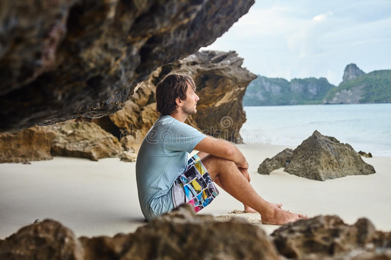 Handsome man sitting on the beach. Relax concept. Handsome man sitting on the beach in cave. Relax concept stock photo
