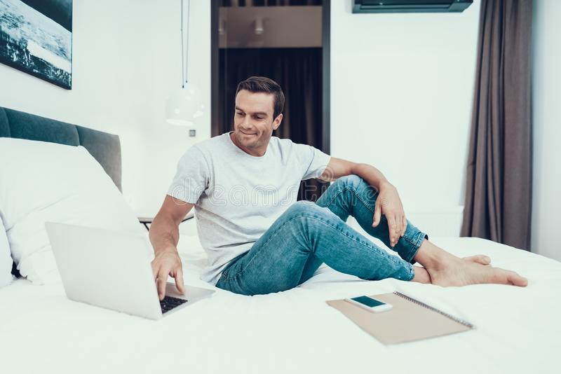 Handsome Man Sitting on Bed and Working on Laptop stock image