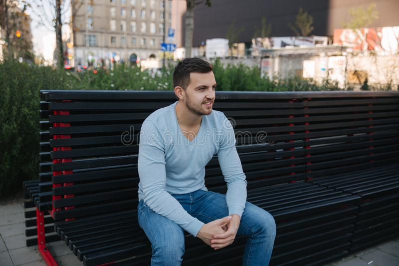 Handsome man sitting on the bench in centre of the city. Happy man outside royalty free stock photos