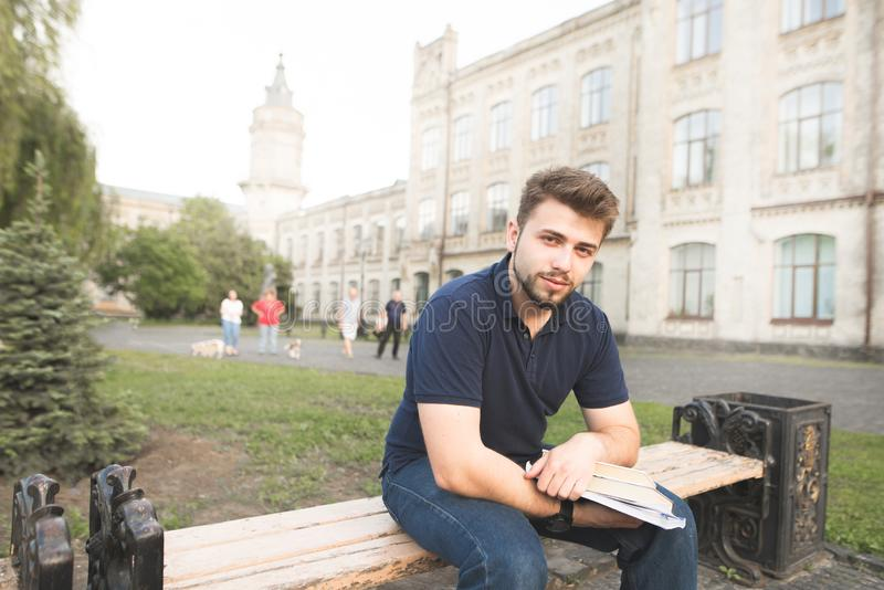 Handsome man sitting on a bench at a university campus with books and looking at the camera. Portrait of a man with a beard on a bench with books in his hands stock image