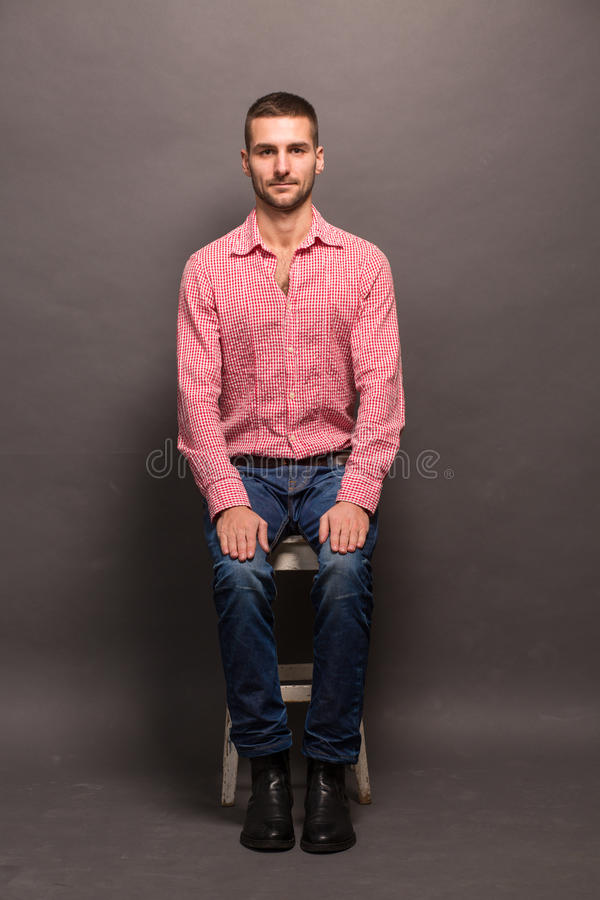 Handsome man sitting on a chair in studio stock image