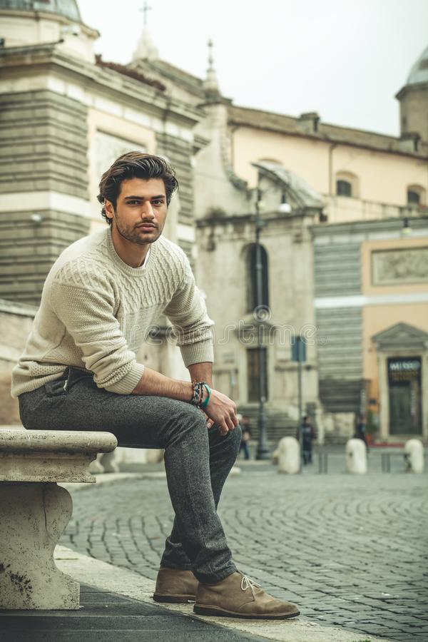 Handsome man sitting in the city center, outdoors. royalty free stock photo