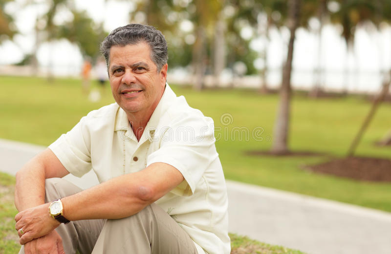 Handsome man sitting in the park royalty free stock photos