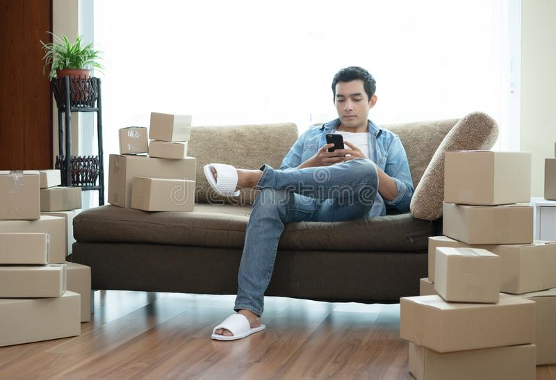 Handsome man sitting on the sofa using smartphone with cardboard. Boxes around him in a new modern home stock photo