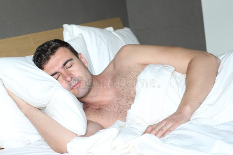 Handsome man sleeping in comfortable bed royalty free stock photos