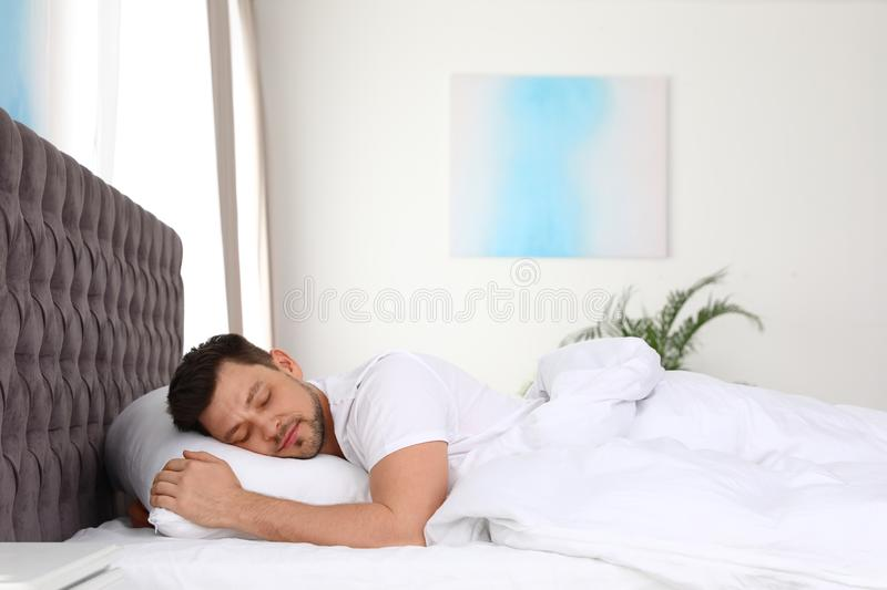 Handsome man sleeping on pillow at home royalty free stock photography