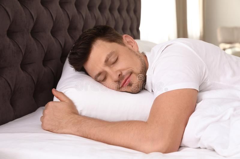 Handsome man sleeping on pillow at home stock photo
