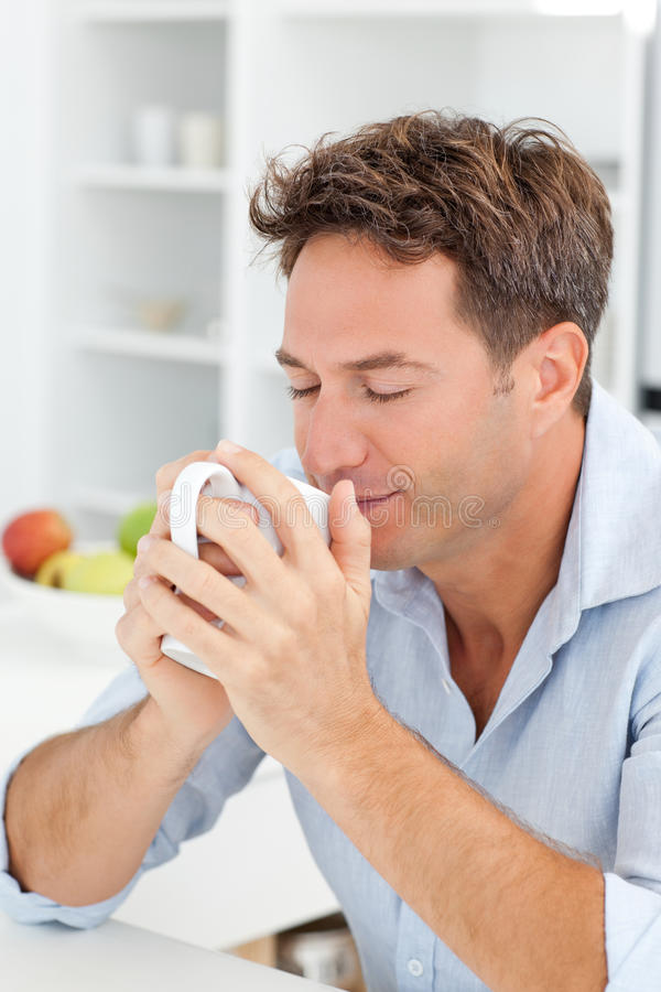 Handsome man smelling his coffee stock photo