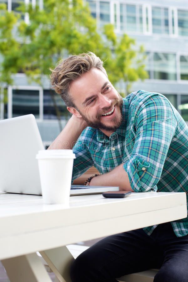 Handsome man smiling outside with laptop stock photos