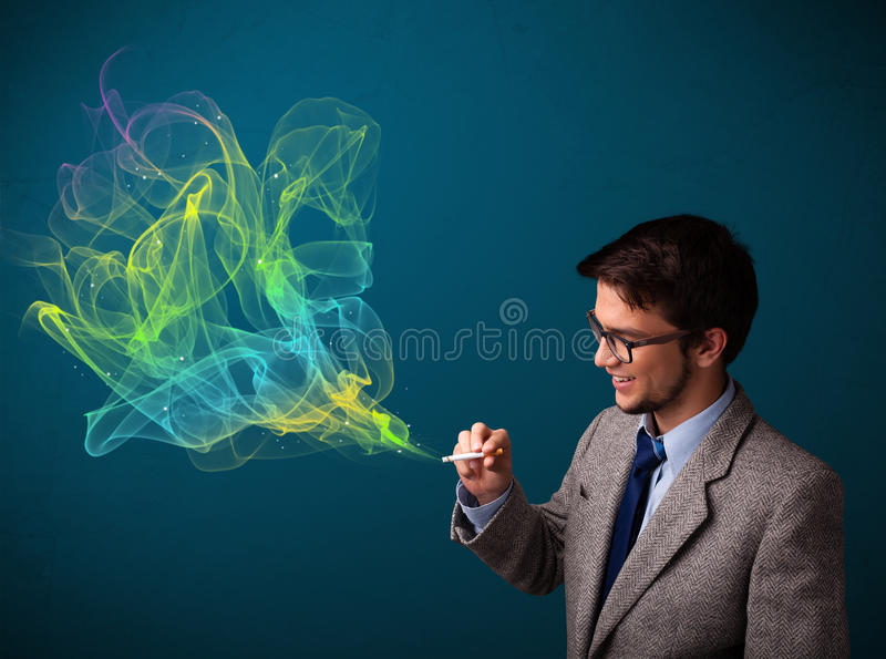 Handsome man smoking cigarette with colorful smoke. Handsome young man smoking cigarette with colorful smoke royalty free stock images