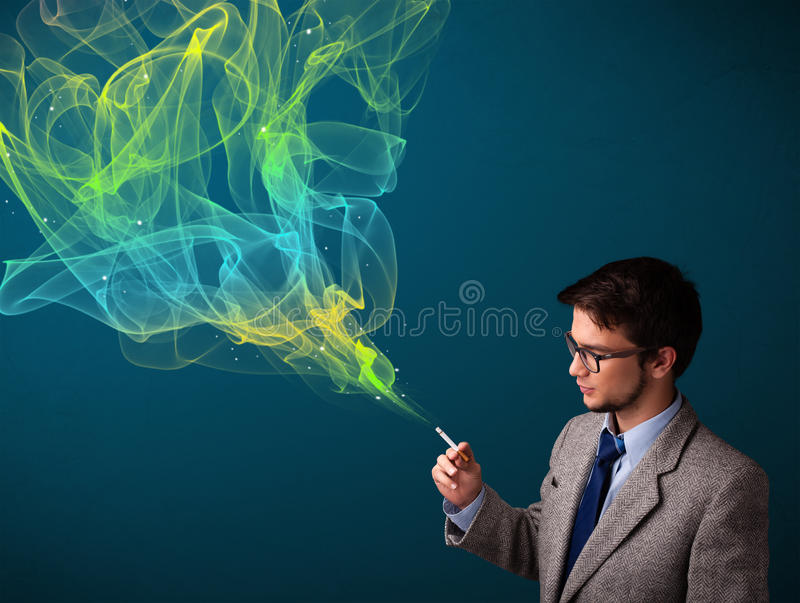 Handsome man smoking cigarette with colorful smoke. Handsome young man smoking cigarette with colorful smoke royalty free stock image