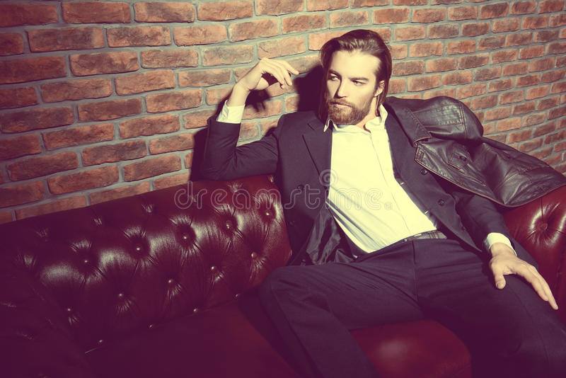 Handsome man on a sofa stock photography