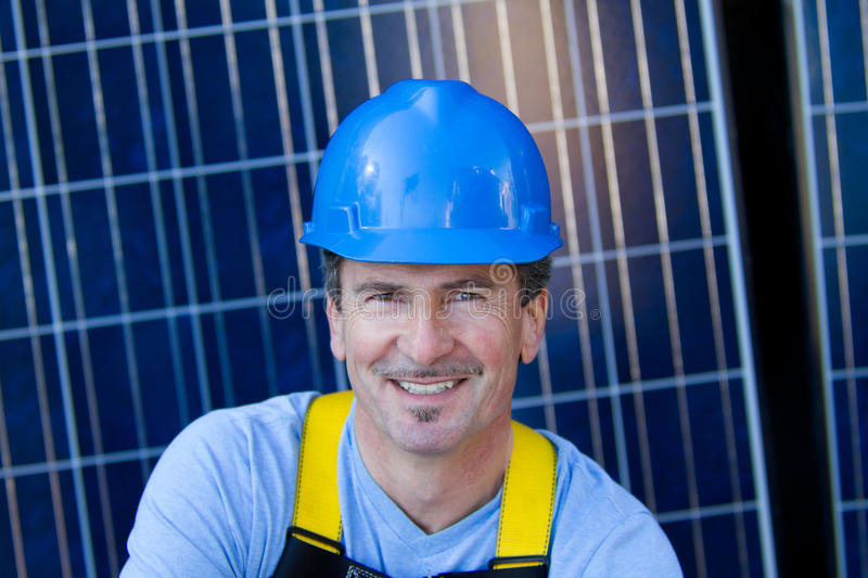 Handsome Man and Solar Panels. Close up of a Man in his forties overseeing a Solar Instalation with Solar Panels behind him stock photography