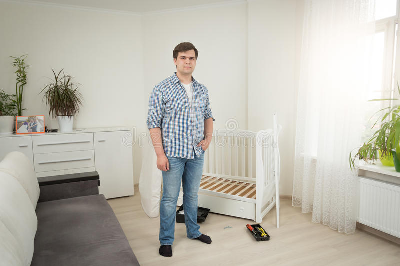 Handsome man standing at disassembled baby crib at bedroom stock images