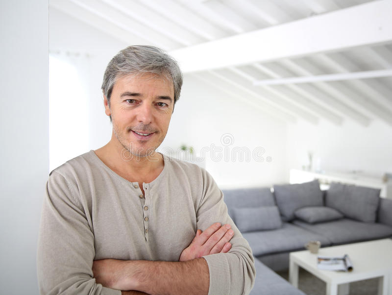 Handsome man standing in living-room stock photography