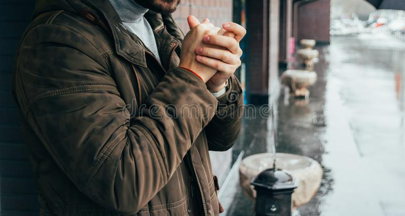 Handsome man standing on the street in winter time and warming his hands. cold day. it`s raining. man in jacket. Town architectur stock images