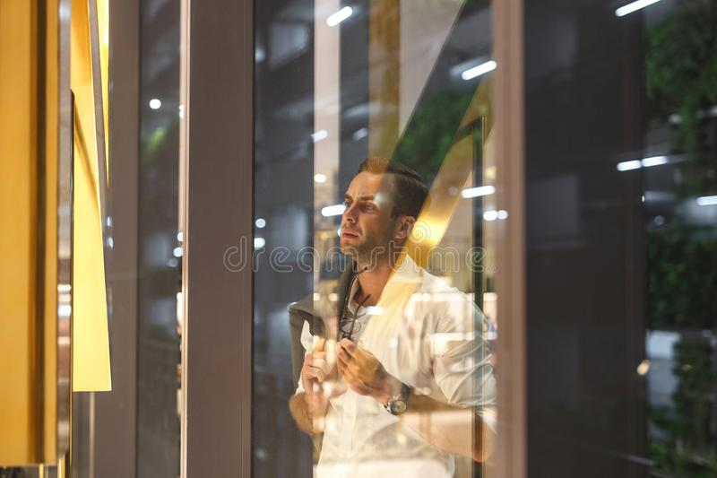 Handsome man stands near the shopping center shop window stock image