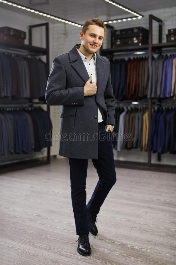 Handsome man stands in suit shop fashionable rich male dressed in expensive clothes posing indoors royalty free stock image