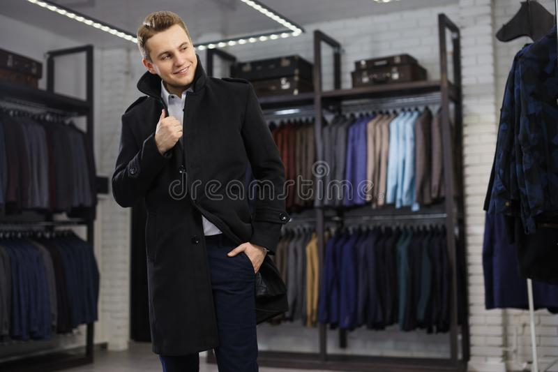 Handsome man stands in suit shop fashionable rich male dressed in expensive clothes posing indoors stock photography