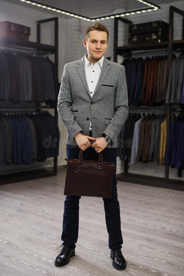 Handsome man stands in suit shop fashionable rich male dressed in expensive clothes posing indoors stock image