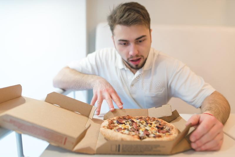 A handsome man stares at the pizza with a hungry look. The man is going to take a piece of pizza. Focus on pizza royalty free stock photography