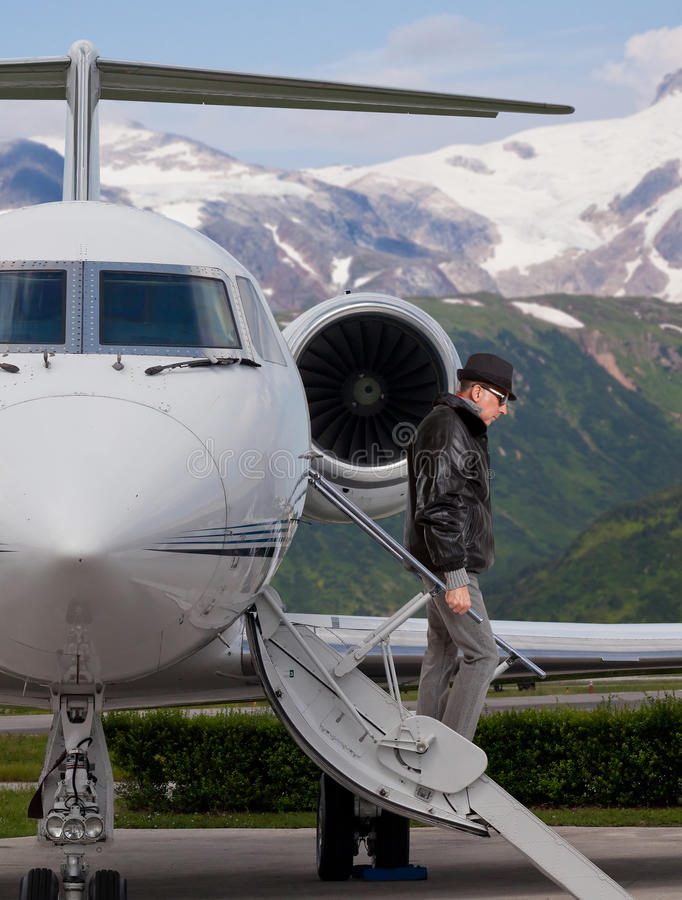 Handsome man on the steps of a private jet stock images