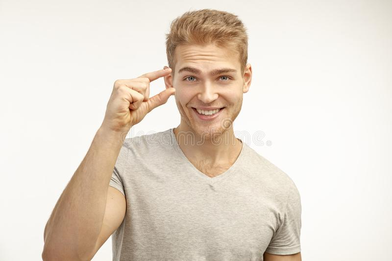 Handsome man with a stylish hairstyle shows a tiny little thing. Demonstrates discounts, sales and small prices for your product. A handsome young man with a stock photography