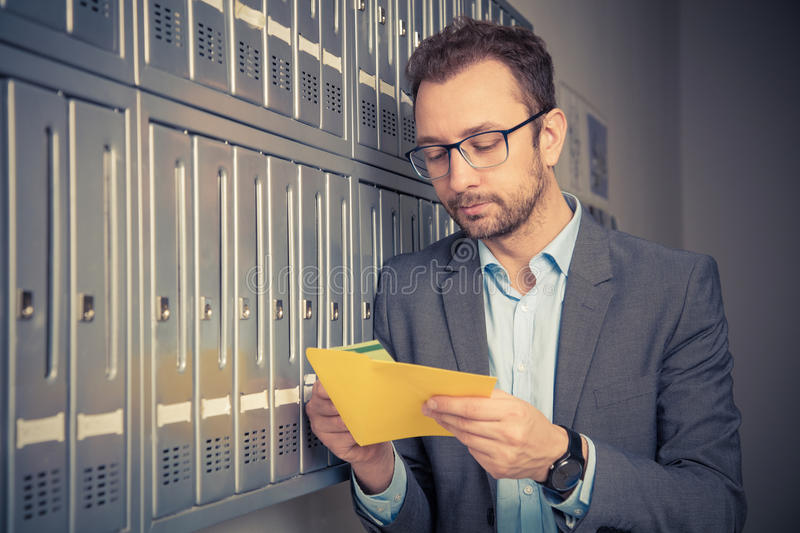 Handsome man in suit checking mail next to the mailboxes. Man reading mail and standing next to the letterboxes royalty free stock images