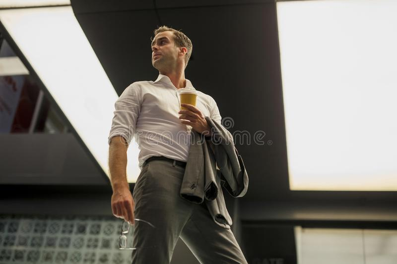 Handsome man in suit with coffee in hand stock photo