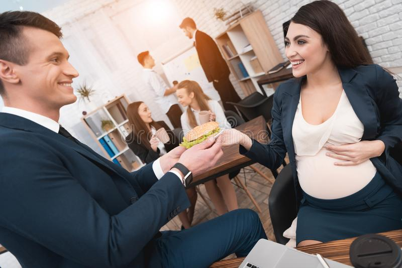 Handsome man in suit gives sandwhich to young pregnant woman in office. Pregnancy at work. stock photography