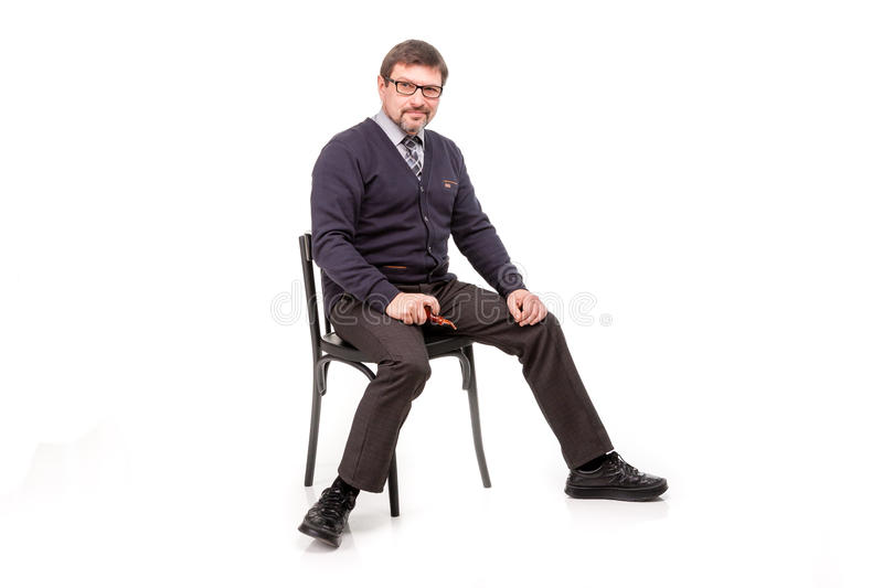 A handsome man in a suit and glasses, sits, with a pipe for smoking; White background stock photo