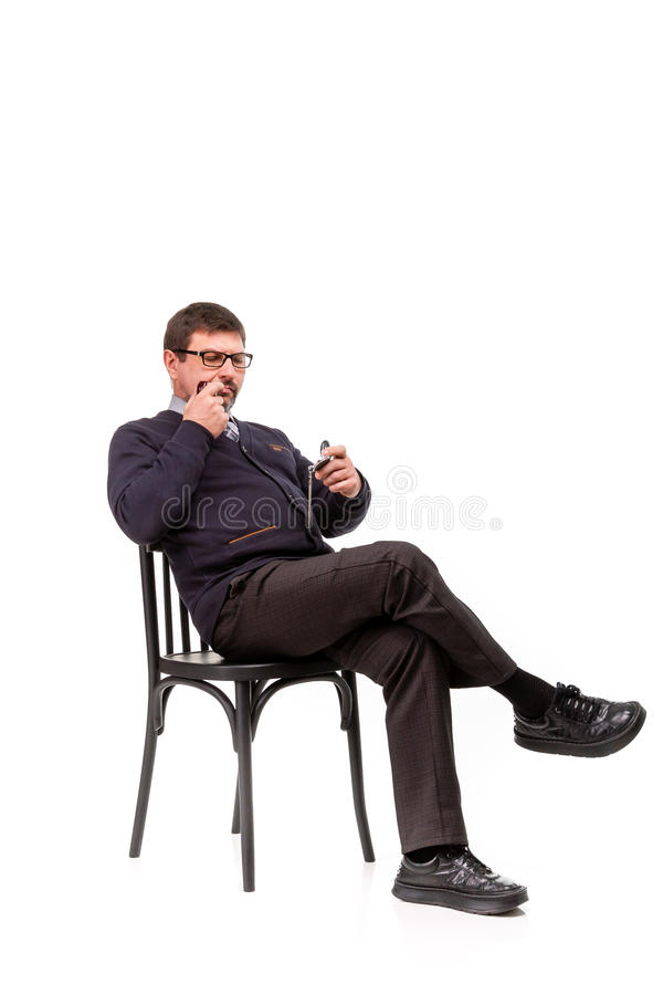 A handsome man in a suit and glasses, sits, with a pipe for smoking; White background royalty free stock images