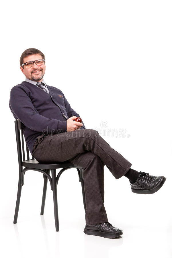 A handsome man in a suit and glasses, sits, with a pipe for smoking; White background royalty free stock photos