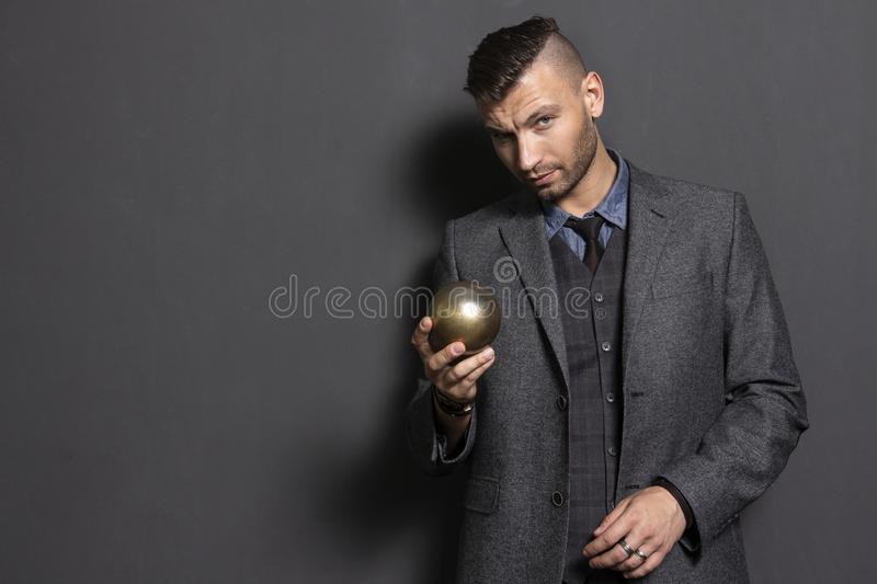 Handsome man in suit holds in hand golden ball. Elegant man business teacher. Fashionable and stylish confident man royalty free stock photography