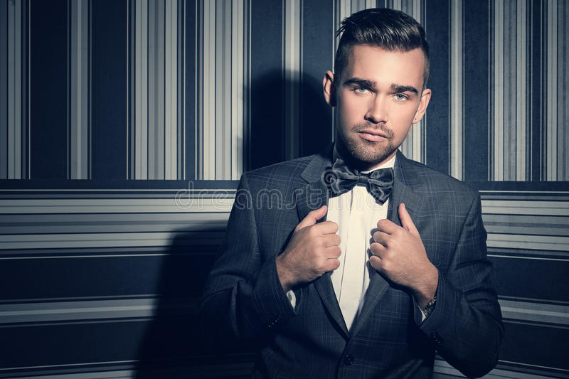 Handsome man in suit. Portrait of a handsome man in a suit and a tie who is posing over a striped background stock images