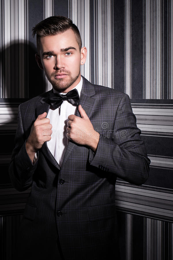Handsome man in suit. Portrait of a handsome man in a suit and a tie who is posing over a striped background royalty free stock images