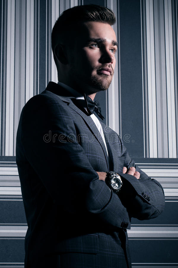 Handsome man in suit. Portrait of a handsome man in a suit and a tie who is posing over a striped background stock photo